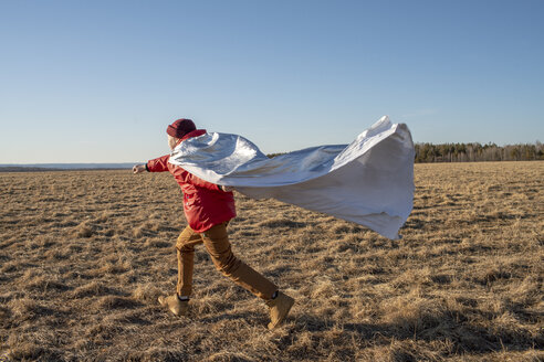 Boy dressed up as superhero running in steppe landscape - VPIF01231