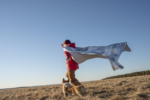Boy dressed up as superhero running with dog in steppe landscape - VPIF01234