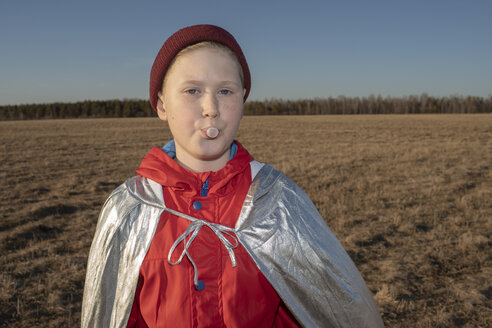 Portrait of boy dressed up as superhero in steppe landscape blowing a chewing gum bubble - VPIF01249