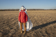 Hood of superhero costume covering boy's face in steppe landscape - VPIF01252