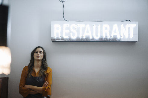 Serious young woman leaning against a wall under restaurant neon light - KNSF05741
