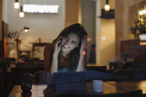 Young woman sitting at table in a restaurant with cell phone and tablet - KNSF05747