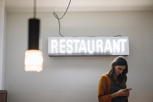 Young woman using cell phone under restaurant neon light - KNSF05753