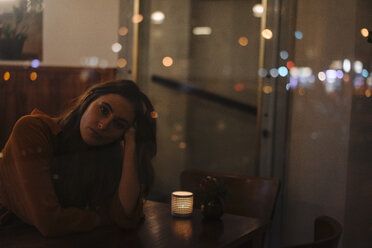 Portrait of young woman behind windowpane in a restaurant - KNSF05756