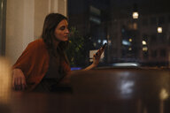 Young woman sitting at table in a restaurant looking at cell phone - KNSF05759