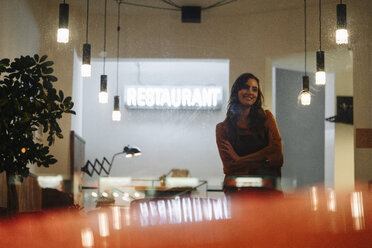 Smiling woman wearing apron standing in a restaurant - KNSF05762
