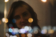 Portrait of smiling young woman behind windowpane - KNSF05765