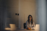 Portrait of serious young businesswoman sitting at desk in office - KNSF05771