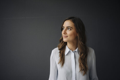Portrait of smiling young businesswoman looking sideways - KNSF05774