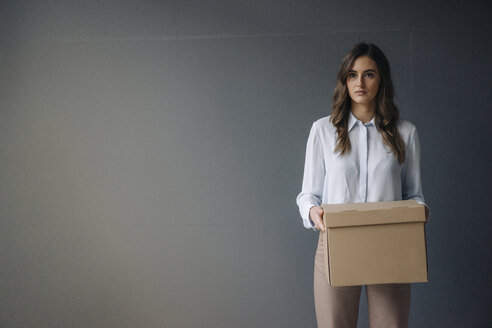 Serious young businesswoman holding cardboard box - KNSF05780