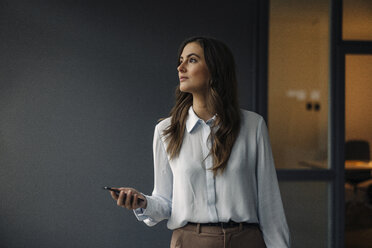 Young businesswoman holding cell phone looking sideways - KNSF05795