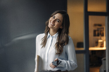 Portrait of smiling young businesswoman holding folder and cell phone - KNSF05798