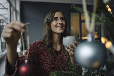 Smiling young woman decorating Christmas tree - KNSF05804