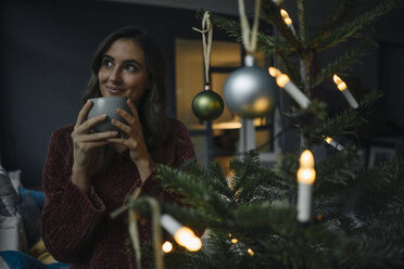 Young woman at decorated Christmas tree holding mug - KNSF05807