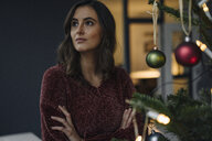 Young woman at decorated Christmas tree looking away - KNSF05810