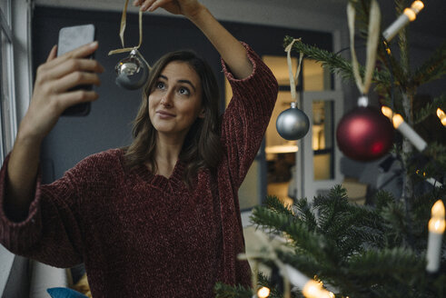 Smiling young woman taking a selfie at Christmas tree - KNSF05813