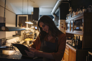 Young woman in restaurant kitchen writing into book - KNSF05819