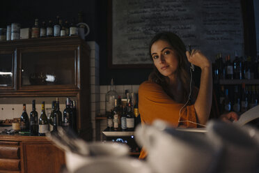 Portrait of young woman with book at restaurant counter - KNSF05822