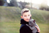Boy carrying puppy outdoors - ISF21250