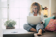 Smiling woman using laptop on couch at home - SIPF01945