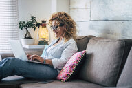 Smiling woman using laptop on couch at home - SIPF01948