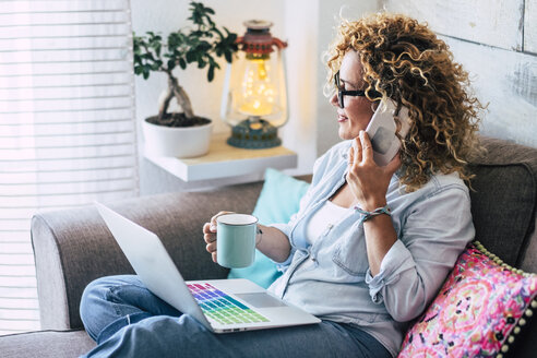 Woman on couch at home with coffee mug, laptop and cell phone - SIPF01951