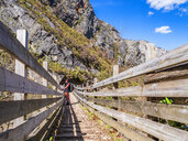 Spain, Asturia, Cantabrian Mountains, senior man on a hiking trip standing on a bridge - LAF02309