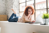 Mid adult woman moving into industrial style apartment, lying on window ledge typing on laptop - CUF50533
