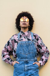 Cool young woman in dungarees and sunglasses standing in front of wall, portrait - CUF50539