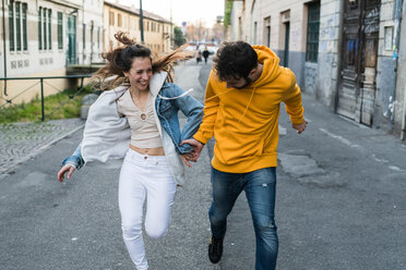 Young couple holding hands running along city alleyway - CUF50542