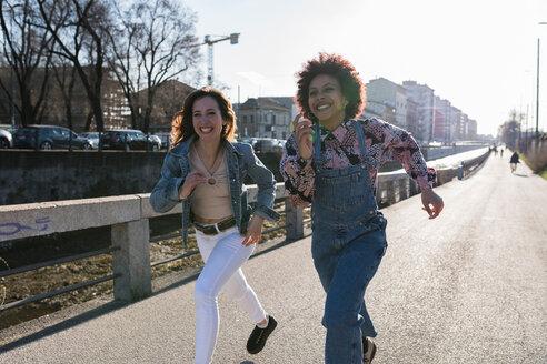 Two young women doing walking race along city road - CUF50551