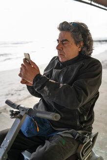 Man on wheels using smartphone at seaside - CUF50566