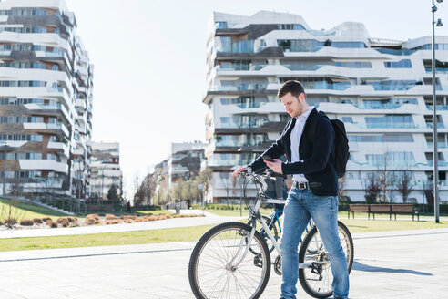 Man pushing bicycle and using smartphone, passing multi-storey building, Milan, Lombardia, Italy - CUF50584