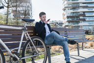 Man talking on smartphone on park bench, Milan, Lombardia, Italy - CUF50587