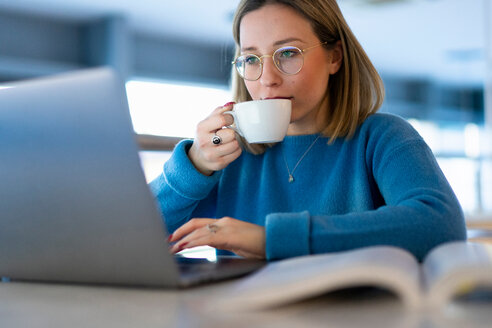 Female higher education student looking at laptop and drinking coffee in university cafe, close up - CUF50614