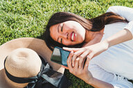 Woman lying down, using smartphone on grass - CUF50632