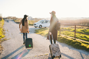 Friends leaving with wheeled luggage on rural road - CUF50647