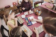 Children painting Easter eggs on table at home - KMKF00926