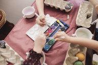 Children painting Easter eggs on table at home - KMKF00929