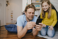 Father and daughter using cell phone in children's room - KNSF05846