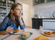 Smiling girl at home sitting at breakfast table - KNSF05849