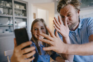 Playful father and daughter taking a selfie at home - KNSF05855