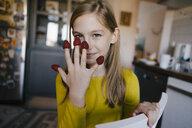 Portrait of a girl with raspberries on her fingertips - KNSF05858