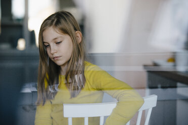 Portrait of a sad girl sitting on chair at home - KNSF05861
