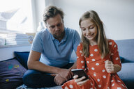 Father and daughter using cell phone at home - KNSF05873