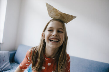 Happy girl balancing paper boat on her head at home - KNSF05876