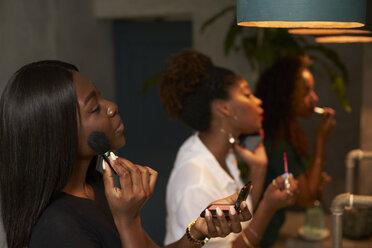 Three friends applying makeup at ladies' room - VEGF00148