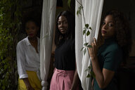 Portrait of three women standing between curtains - VEGF00157
