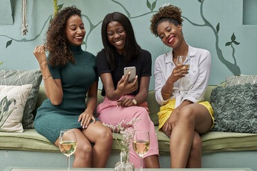 Portrait of three laughing friends looking at cell phone - VEGF00166