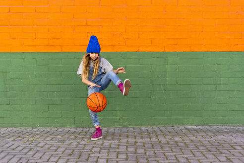 Young girl playing basketball, dribbling and lifting leg - ERRF01230